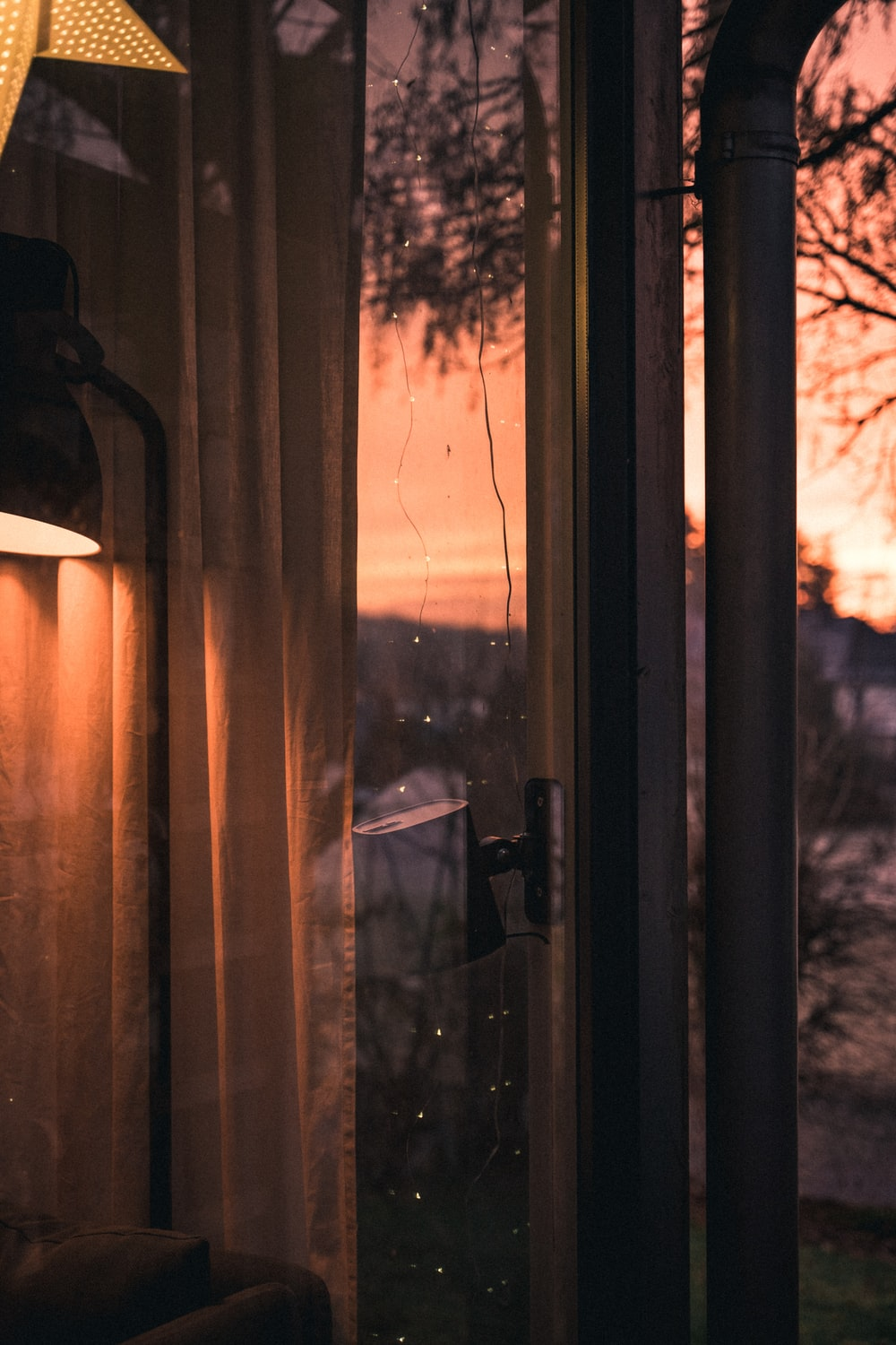 brown curtain on glass window during sunset