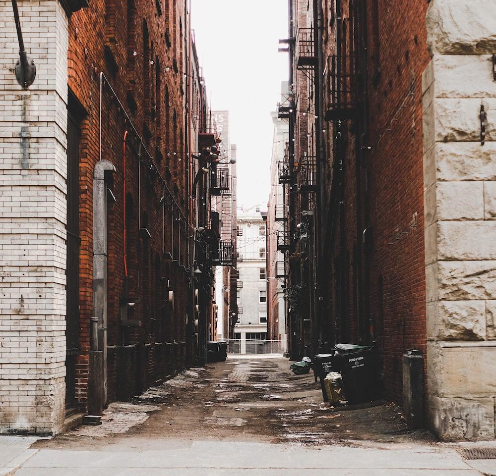 black wooden bench in between brown brick buildings during daytime
