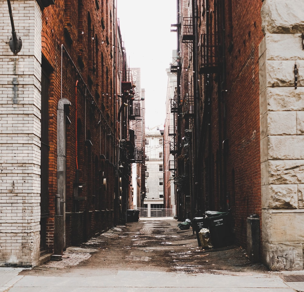 black wooden bench in between brown brick buildings during daytime
