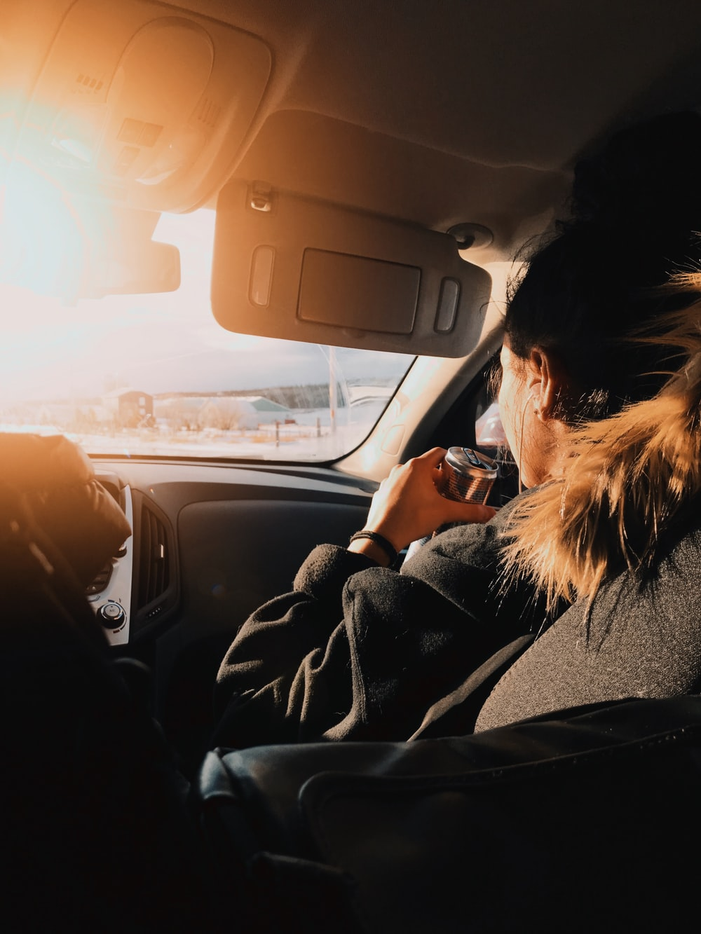 woman in black jacket driving car during sunset