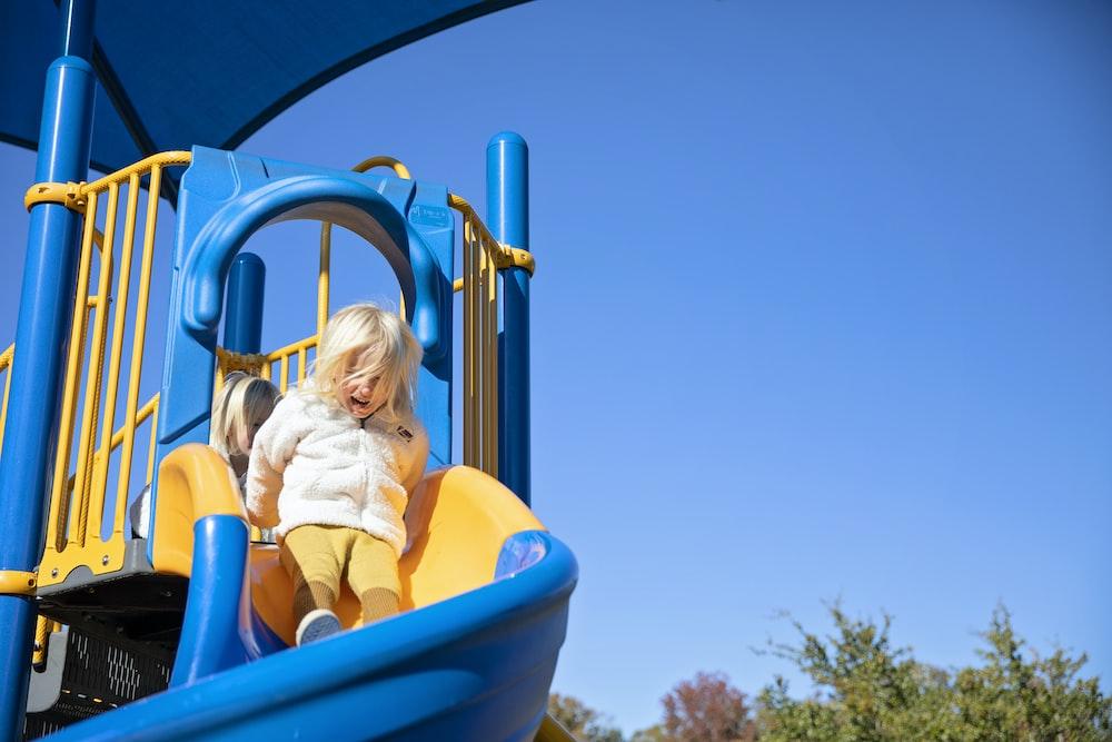 girl in yellow shirt riding blue plastic slide during daytime