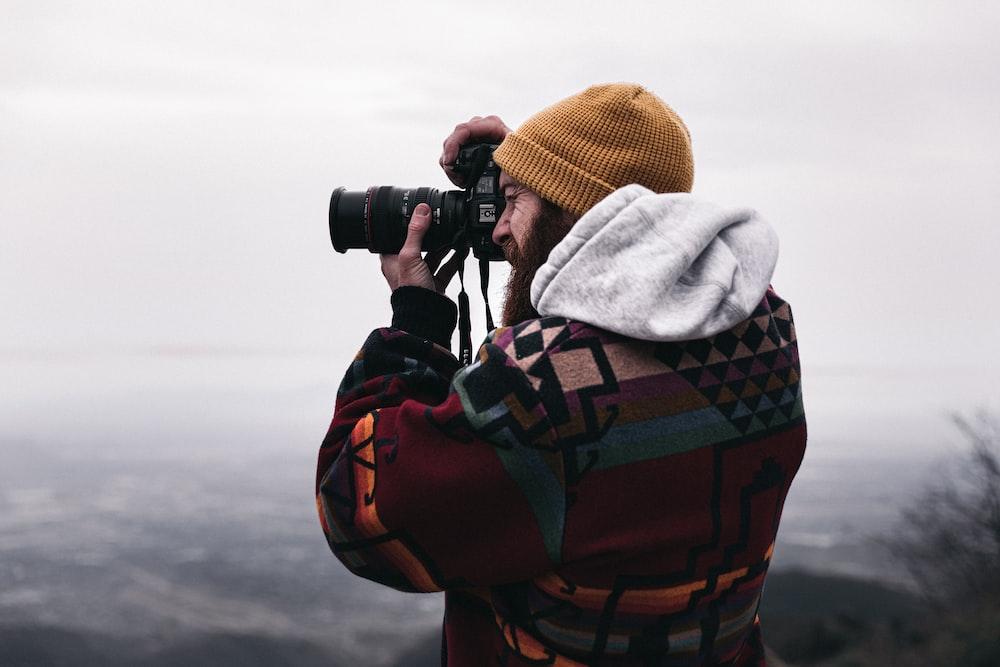 person in gray hoodie using black binoculars