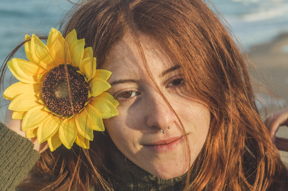 woman with yellow sunflower on her ear
