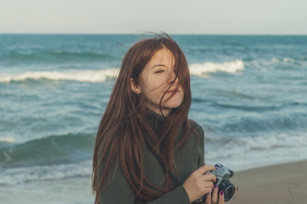 woman in brown turtleneck sweater holding black dslr camera