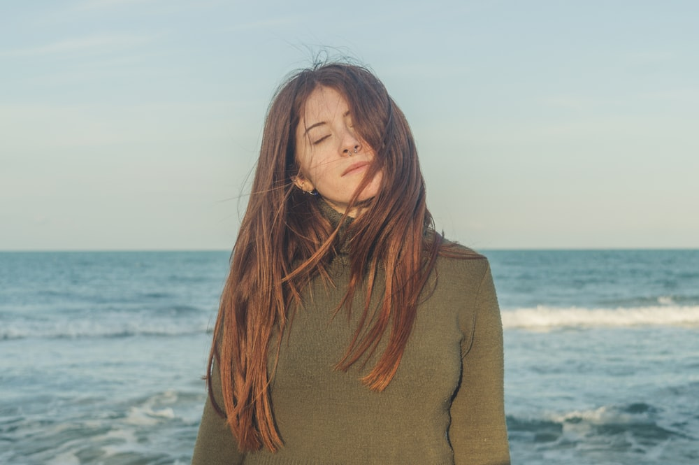 woman in brown turtleneck sweater standing near sea during daytime