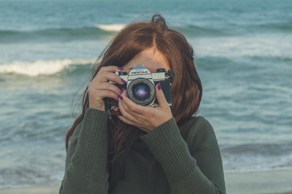 woman in gray sweater holding camera