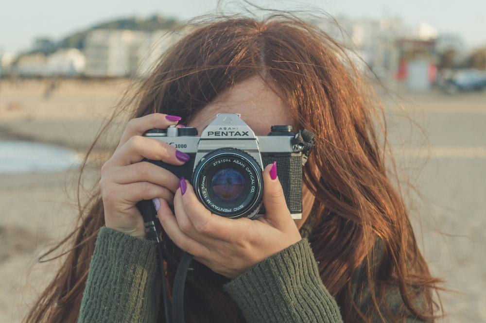 woman holding black and silver nikon dslr camera
