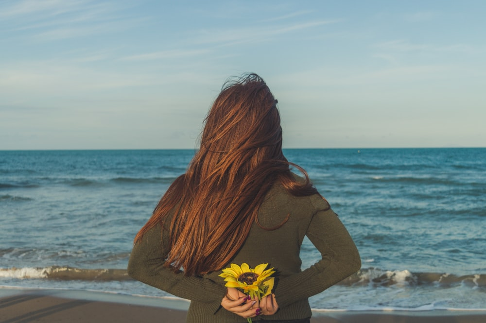 woman in black long sleeve shirt sitting on beach shore during daytime