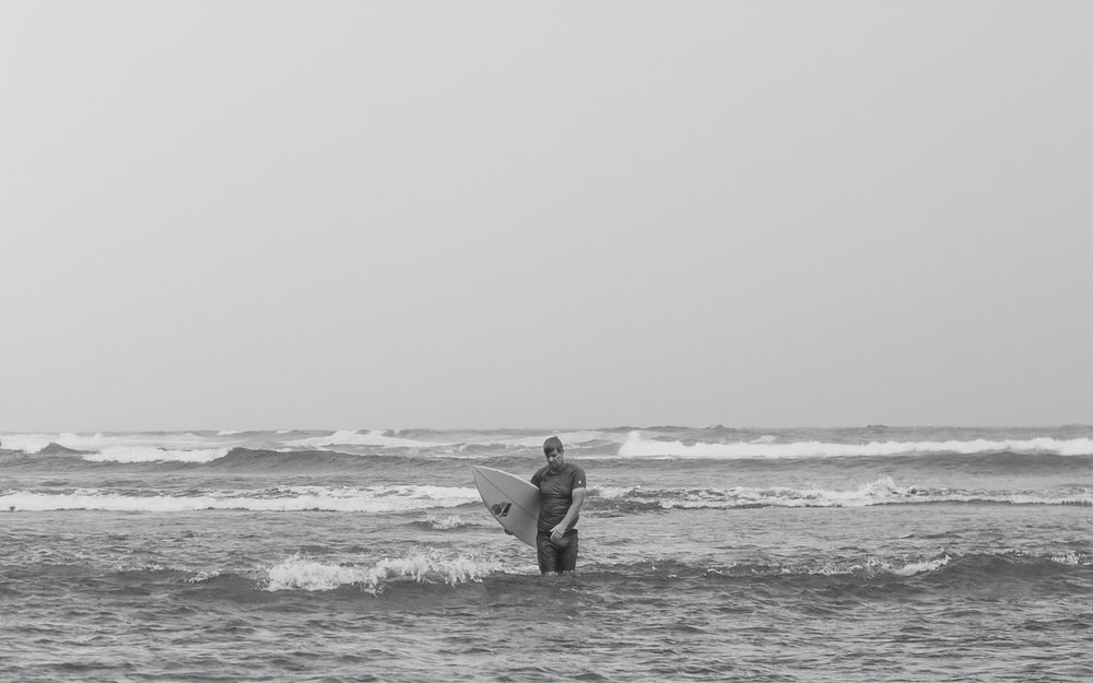 grayscale photo of man holding surfboard on beach