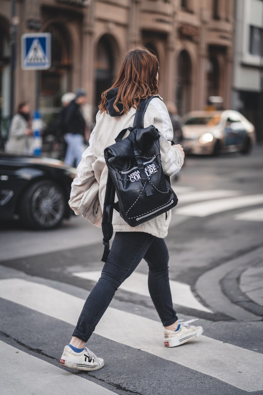 woman in black pants and white jacket walking on sidewalk during daytime