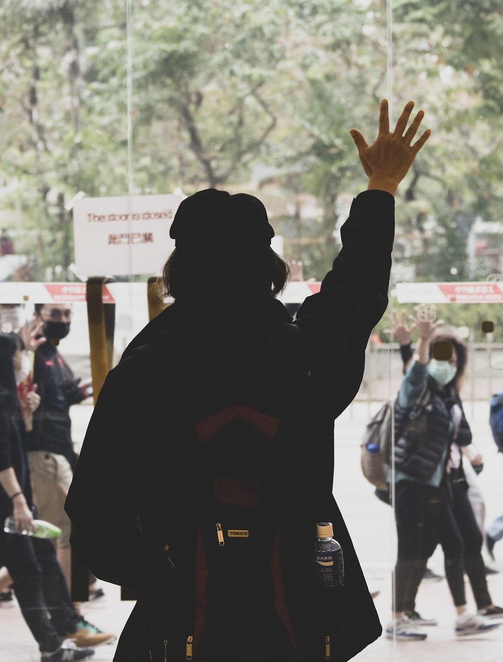 man in black hoodie raising his hands