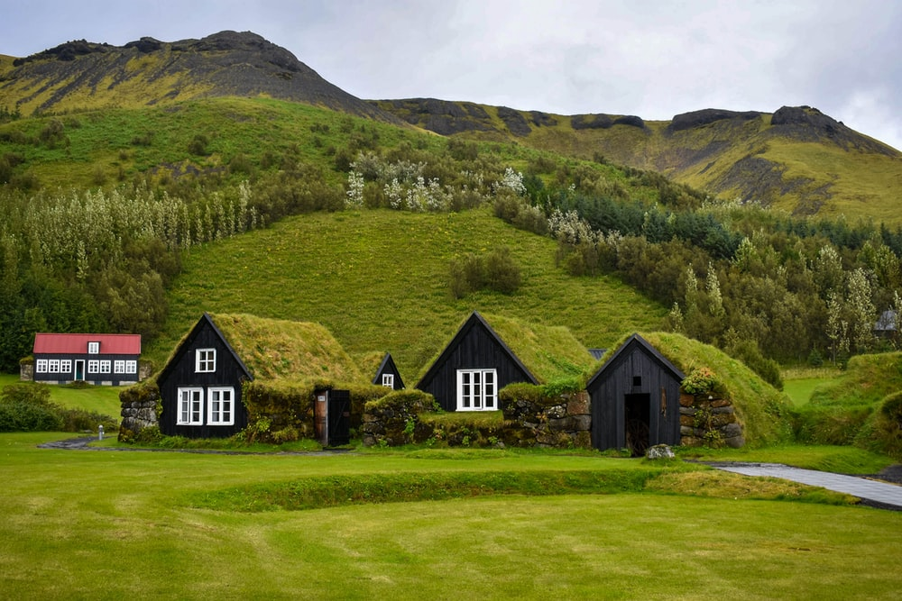 brown and black house on green grass field near green mountain under white clouds during daytime