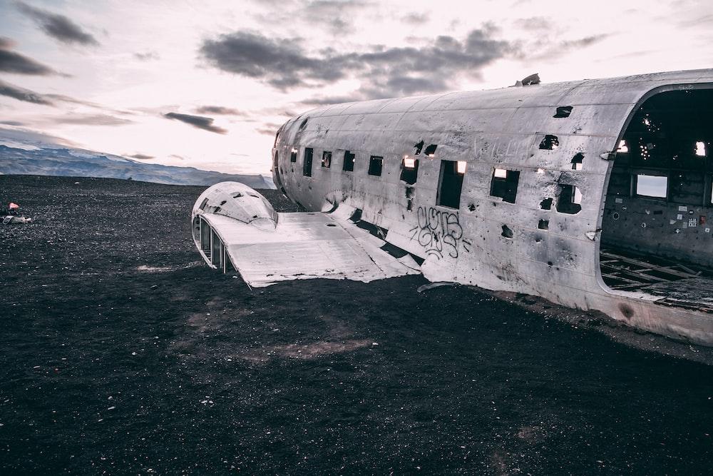 white airplane on black sand during daytime