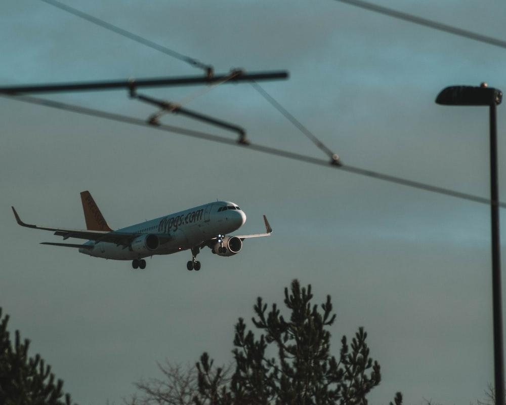 white and blue passenger plane flying during daytime