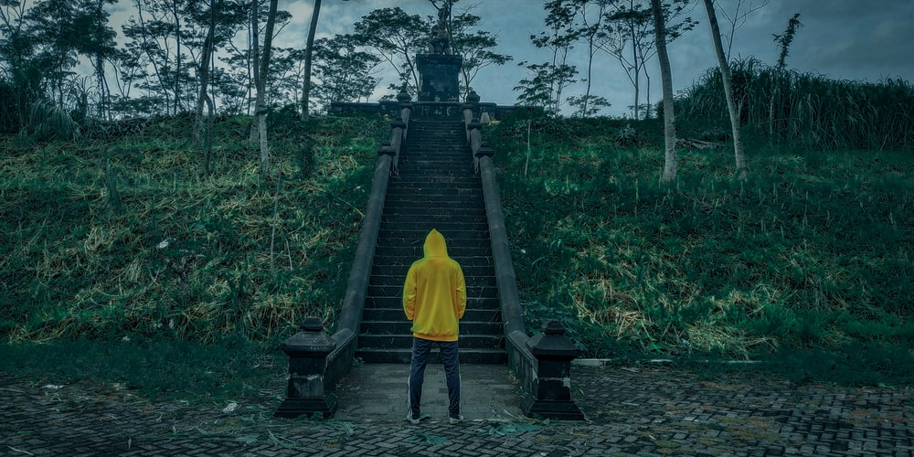 person in yellow hoodie walking on wooden bridge