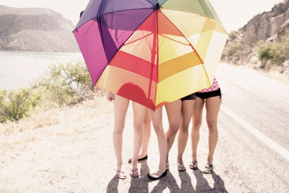 3 women in red and yellow umbrella walking on gray sand during daytime