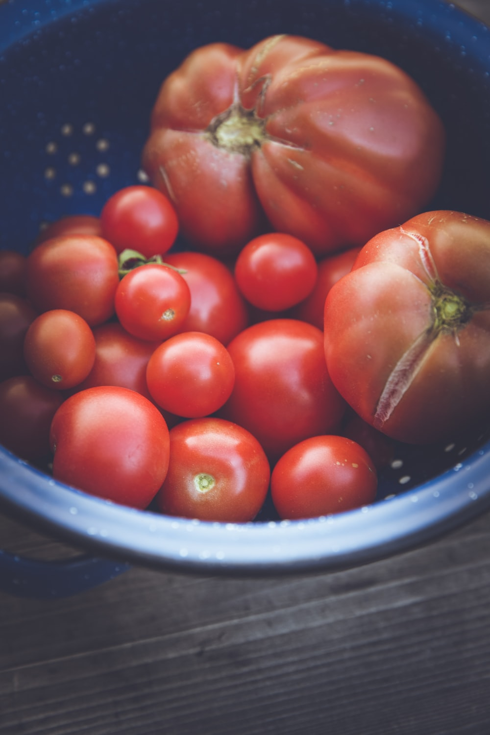 red tomatoes on blue plastic bowl