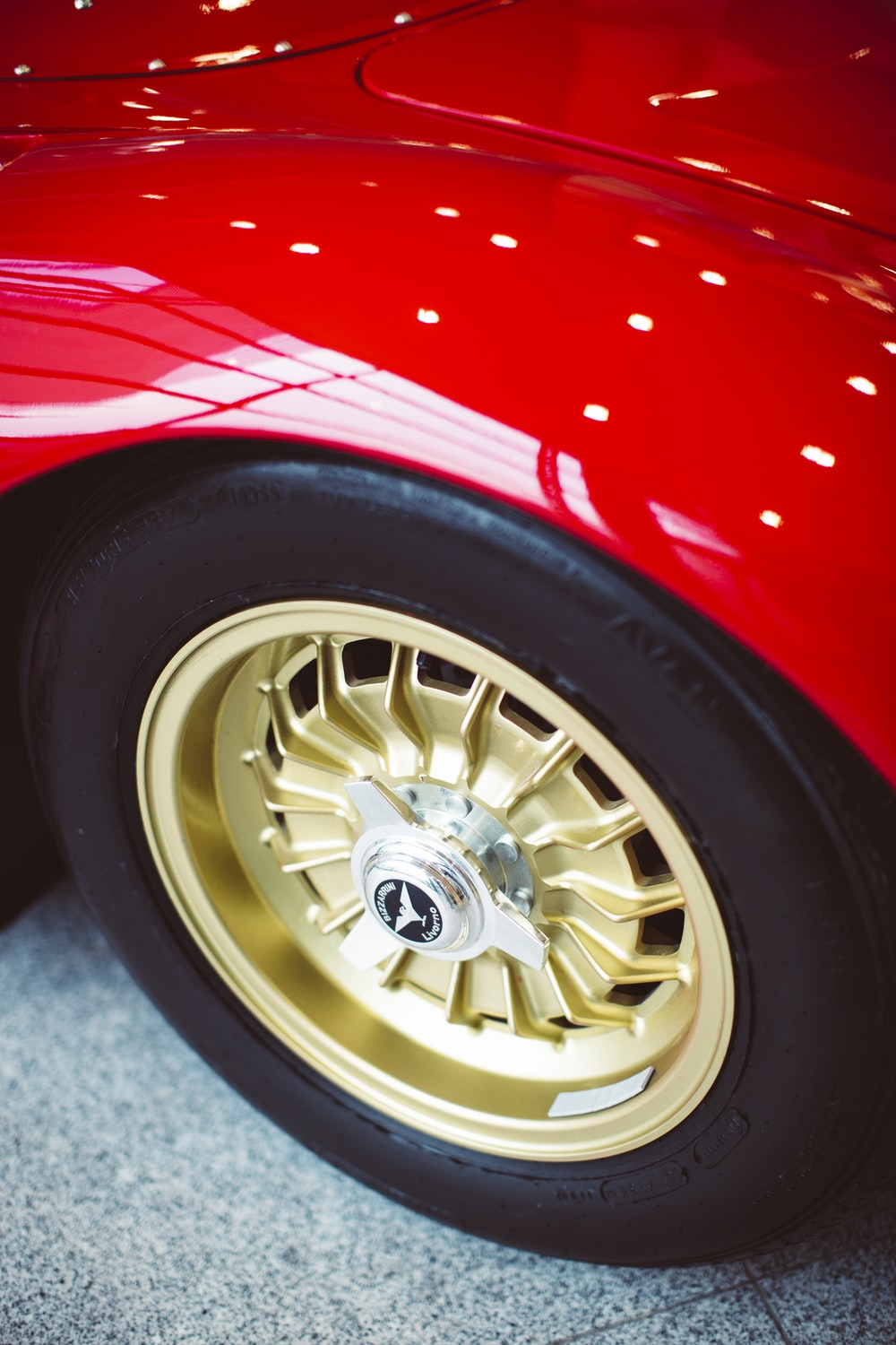 silver and gold wheel with tire