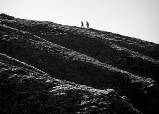 grayscale photo of person walking on hill