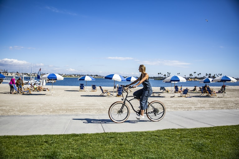 woman in black tank top riding on bicycle on gray concrete road during daytime