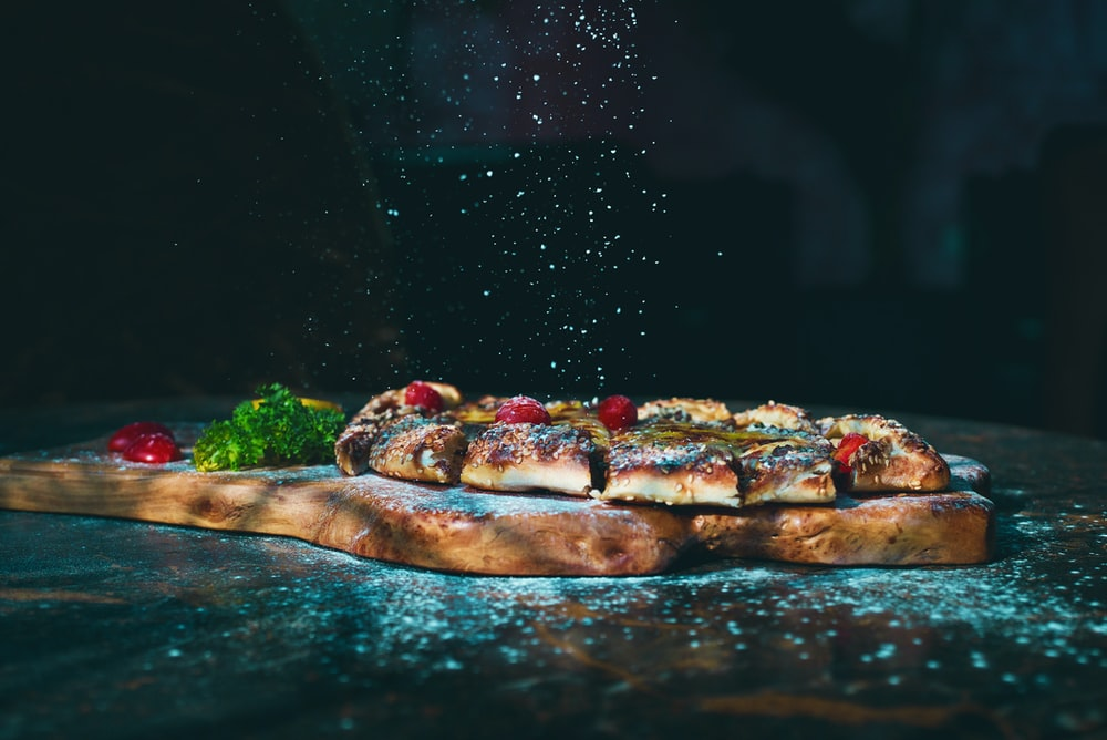 brown and red pizza on brown wooden table