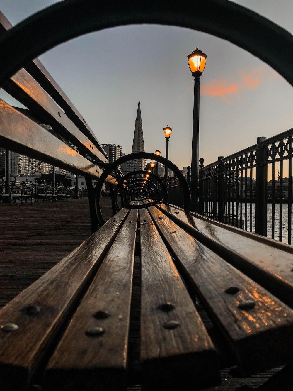 brown wooden bench near black metal railings during daytime