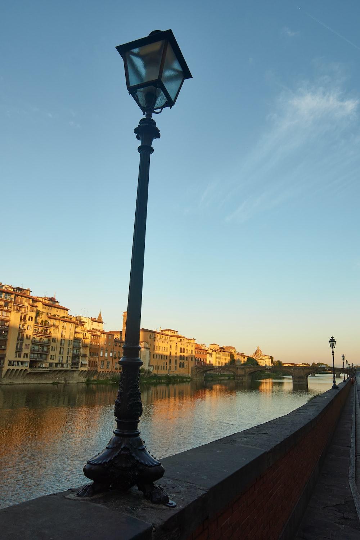black street lamp near river during daytime