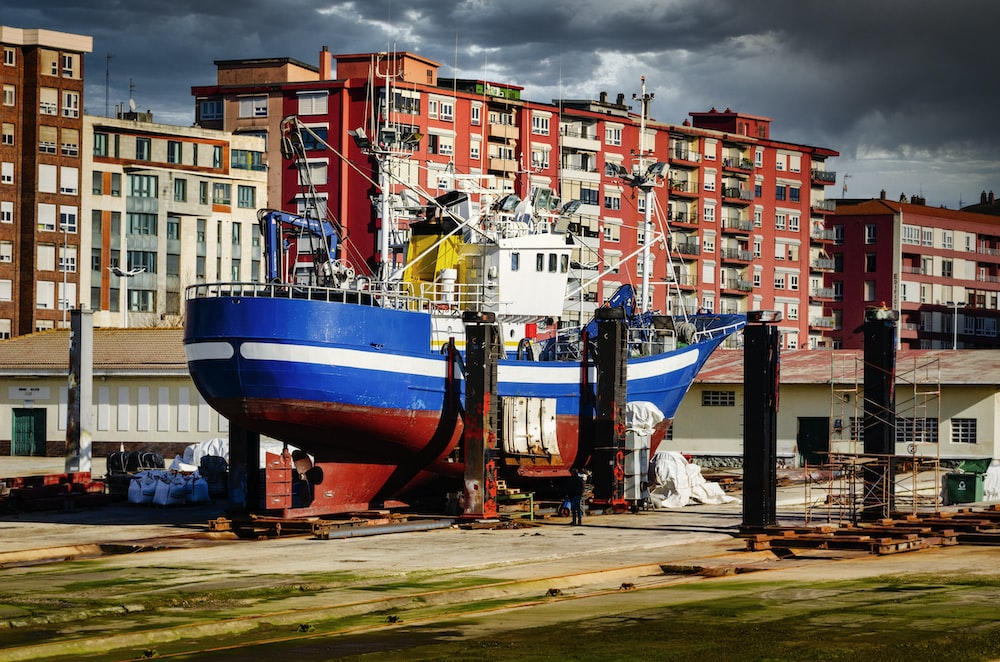red blue and white boat on brown sand near city buildings during daytime