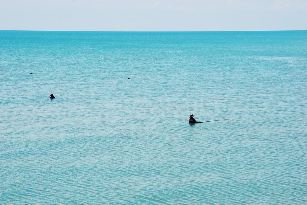 man in black wet suit riding on boat on sea during daytime