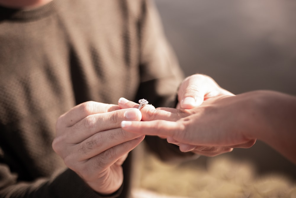person holding silver diamond ring