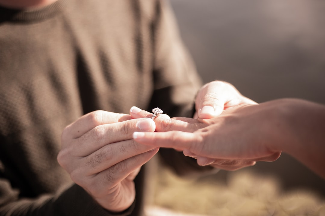 Close up of a man holding a woman's hand and ring during a proposal