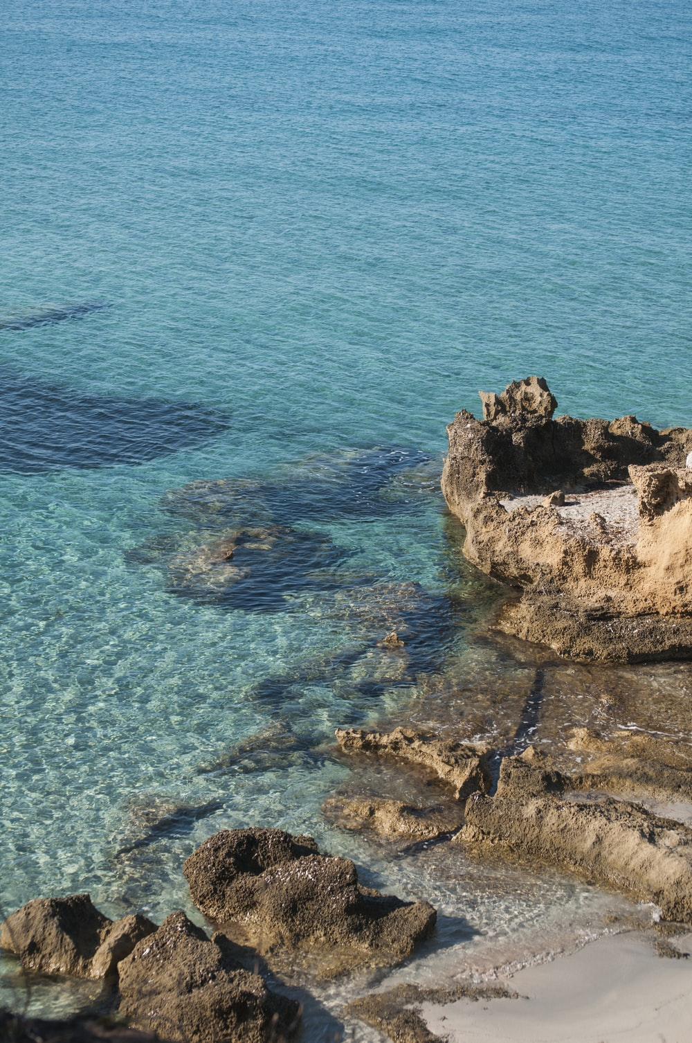 brown rock formation on blue sea during daytime