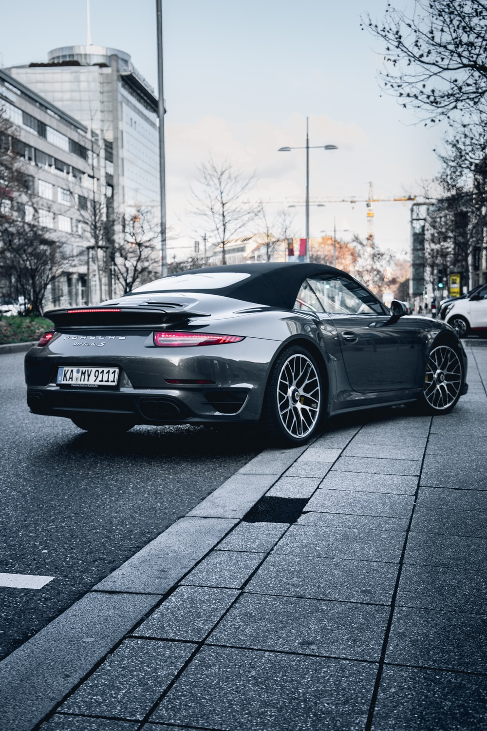 Dark gray Porsche 911 driving around a corner