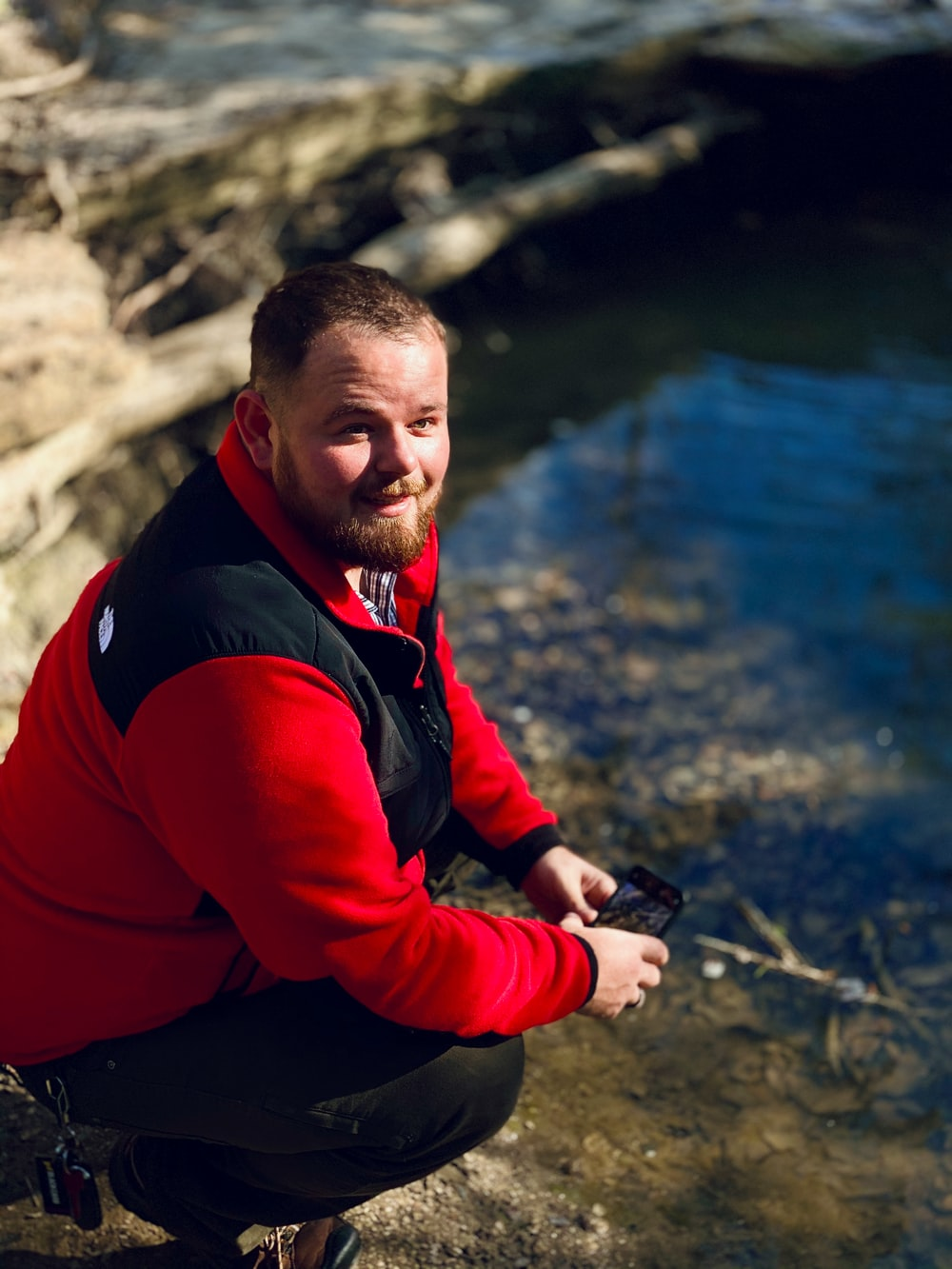 man in red and black long sleeve shirt sitting on rock