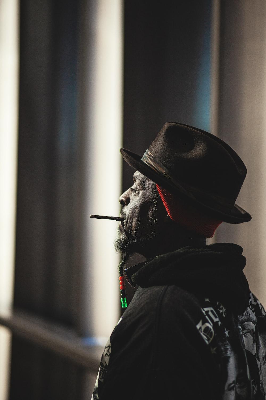 man in black jacket wearing black hat