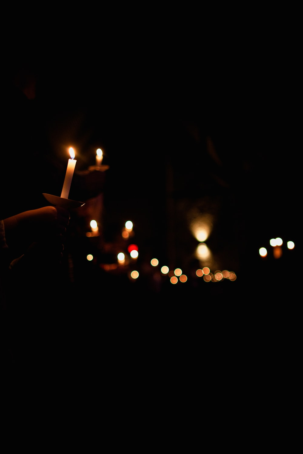 person holding lighted candle during night time