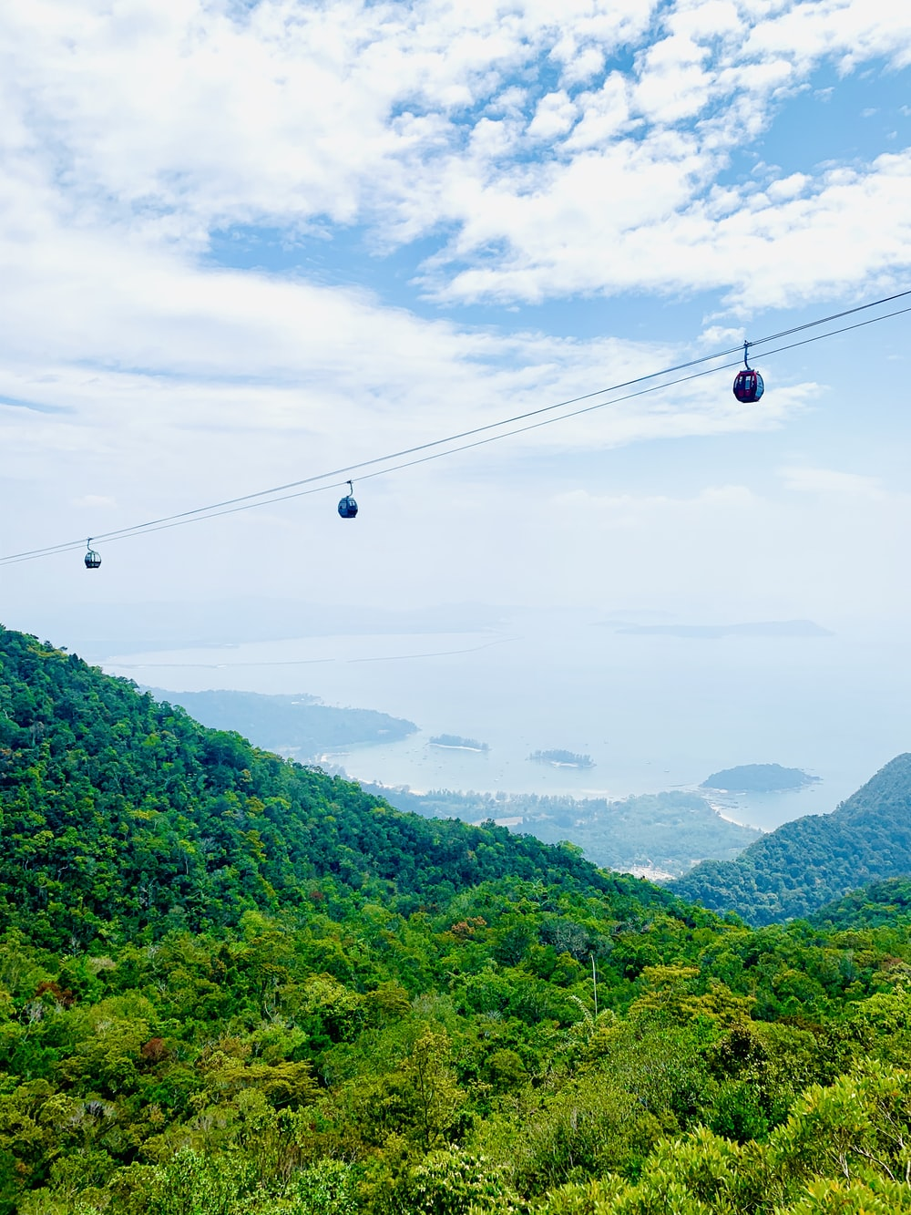 cable cars over green mountains during daytime