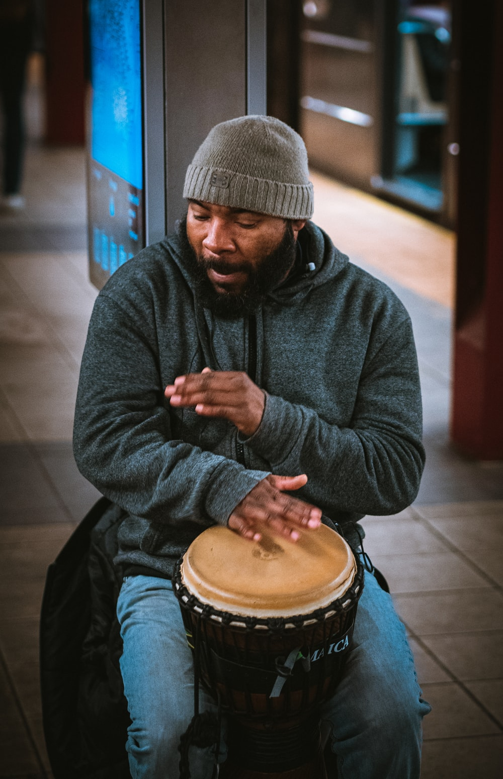 man in black knit cap and black jacket playing drum