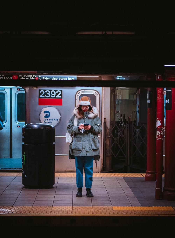 woman in gray jacket standing beside black trash bin