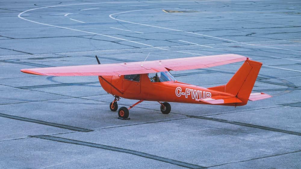 red and white airplane on gray concrete ground during daytime