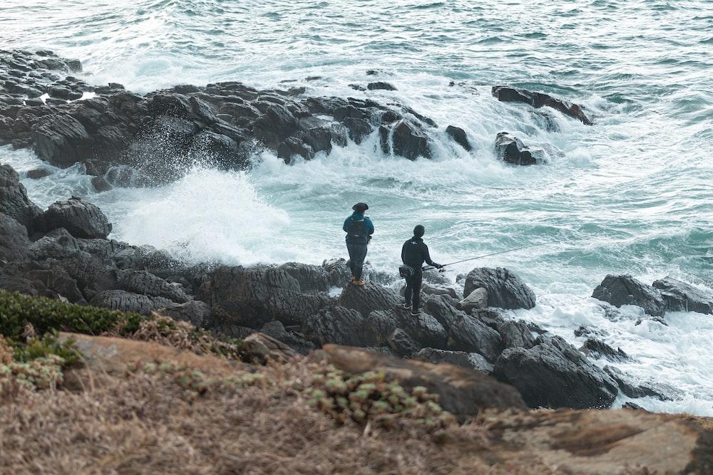 man in black jacket standing on rock near sea waves during daytime