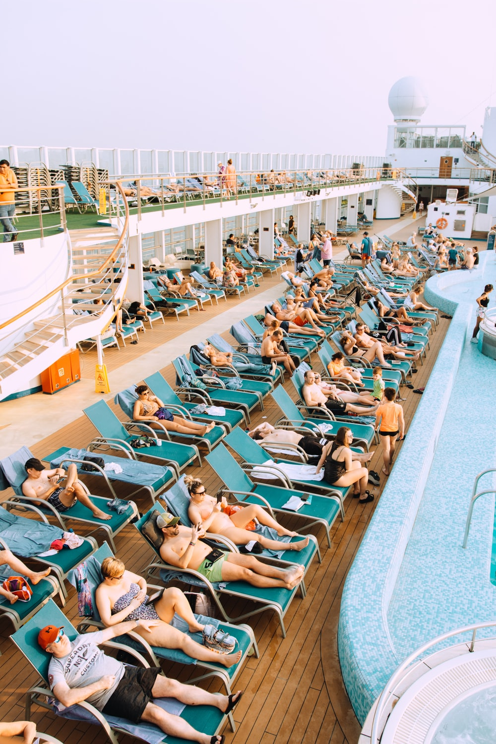 people lying on blue and white lounge chairs