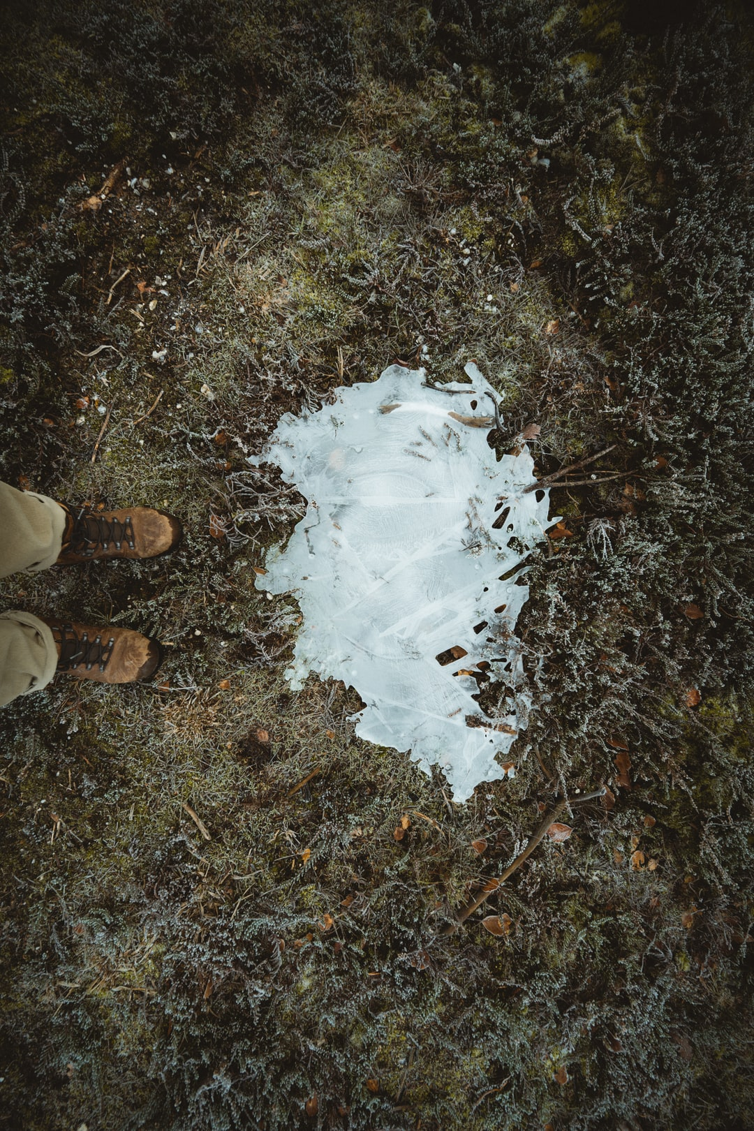 Hikers boots by an icy puddle
