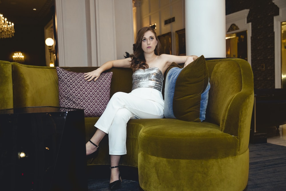 woman in white dress lying on couch