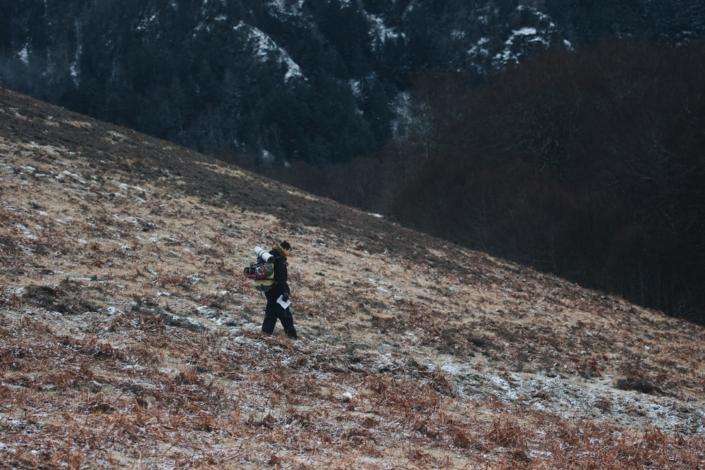 person in black jacket walking on brown dirt road during daytime