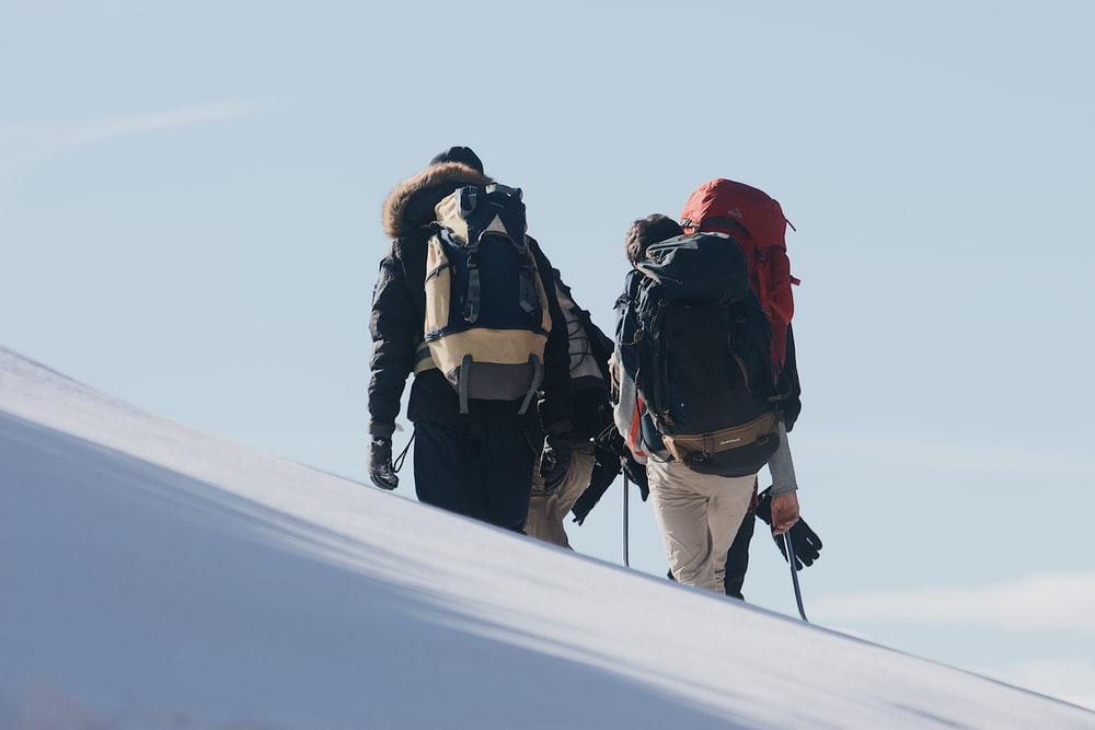 3 person in black jacket and red knit cap standing on snow covered ground during daytime