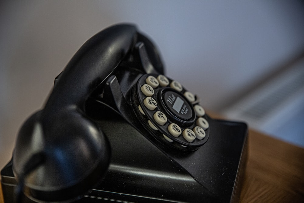 black rotary telephone on black table