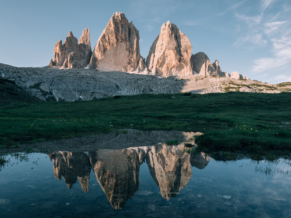 gray rocky mountain near green grass field during daytime