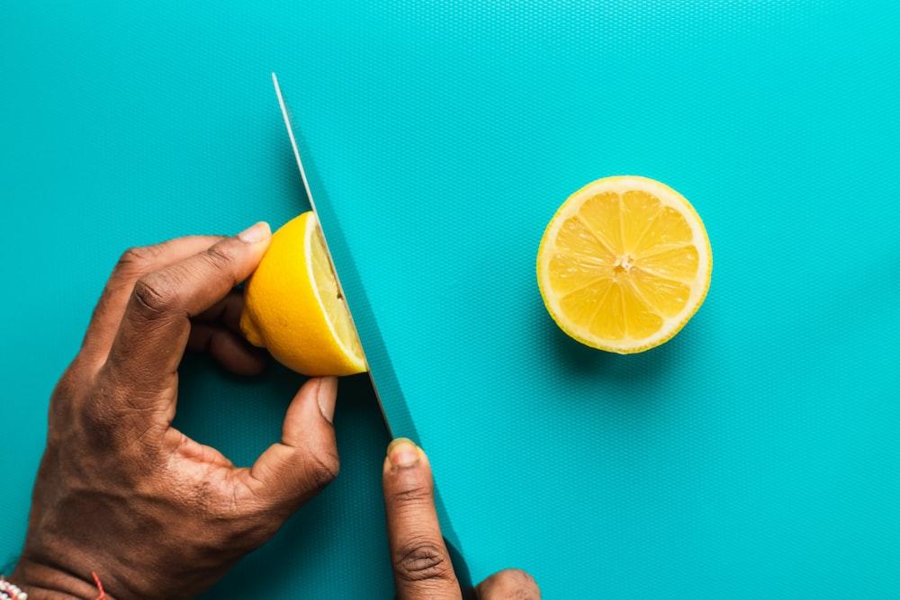 person holding sliced lemon fruit