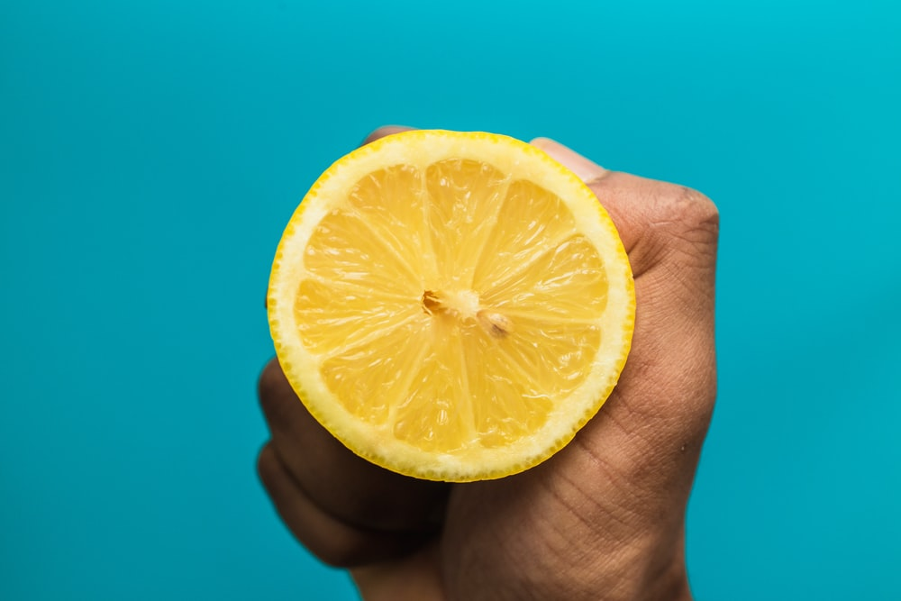 person holding sliced lemon fruit